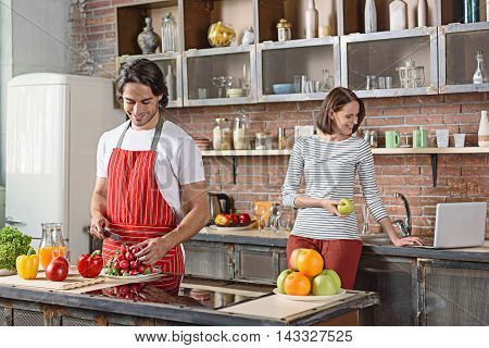 Cheerful young husband and wife preparing healthy food in kitchen. Man is standing near table and cutting vegetable. Woman is reading recipe on laptop and smiling