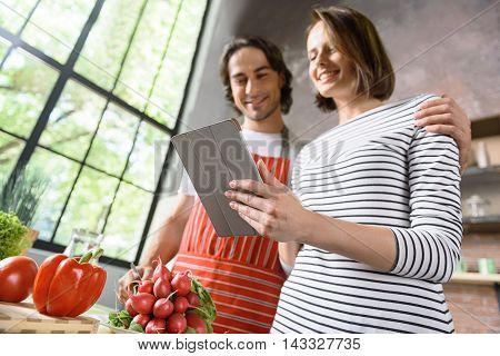 Married couple is cooking healthy food in kitchen. Woman is standing and reading recipe on tablet with interest. Man is embracing her and smiling