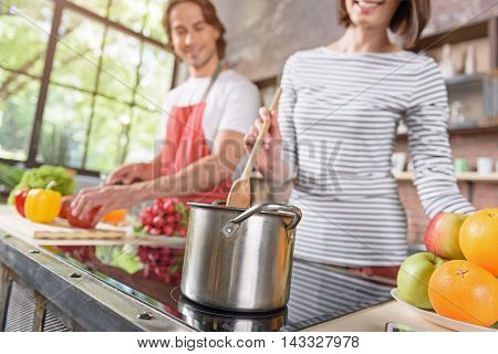 Joyful married couple is cooking together at home. Woman is mixing meal in pot and smiling. Man is standing and cutting vegetables