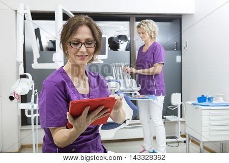 Assistant Using Digital Tablet While Colleague Working At Dentis