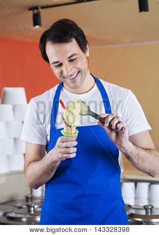 Smiling Waiter Preparing Vanilla Ice Cream