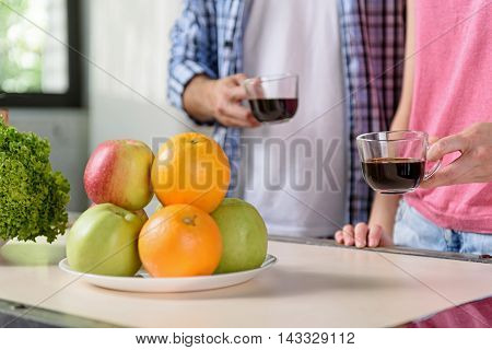 Close up of young married couple having breakfast in kitchen. They are standing near table and holding cups of coffee. Focus on fresh fruits in plate