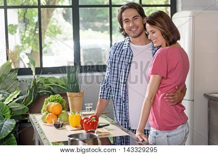 We like cooking together. Joyful husband and wife are standing in kitchen and embracing. They are smiling with happiness