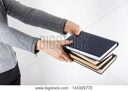 Hands holding books on white background, education background.