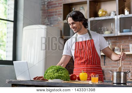 Happy young man is using laptop while cooking at home. He is standing and mixing dish in pot. Man is smiling