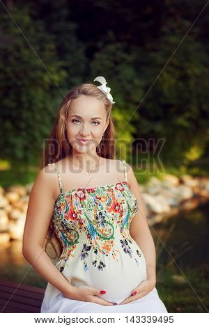 Beautiful pregnant woman in a floral dress sits in a Park outdoors in summer supporting abdomen with hands. A young expectant mother looks straight into the camera and smiling