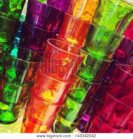 Stacks of colorful plastic glasses. Orange green red and purple.