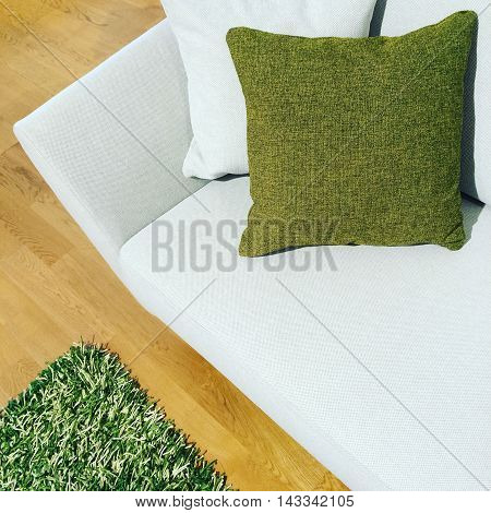 White sofa with green cushion and fluffy rug on a wooden floor.