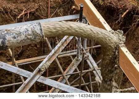 Concrete pumping hose filling a reinforced foundation hole