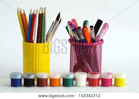 A set of colored pencils and a set of colored paints for children's creativity.