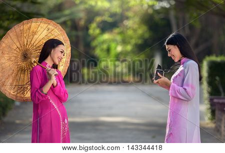 Portrait of Vietnamese girl traditional dress with camera
