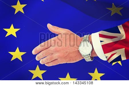 Businessman in suit clenching fists against digitally generated great britain national flag
