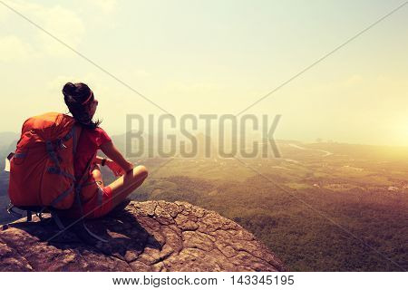 young woman hiker enjoy the view at mountain peak cliff
