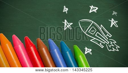 Colourful crayons against green chalkboard