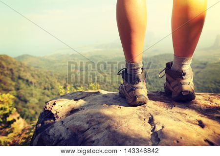 hiker legs climbing at mountain peak rock