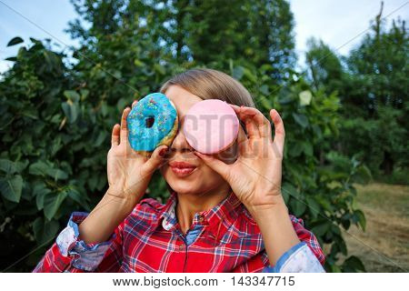 Funny girl holding a donut in his hand. She made glasses of donuts. Delicious.