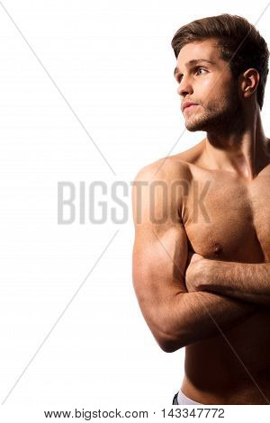 Beauty of masculine form. Cropped image of serious muscular man posing on white background in studio