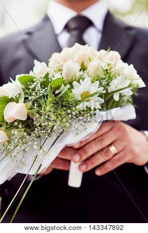 Bouquet Of Wedding Flowers Close To The Groom's Hands