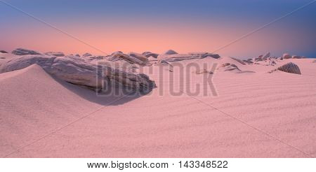 A ground level view of a deserted beach with a pink sunset