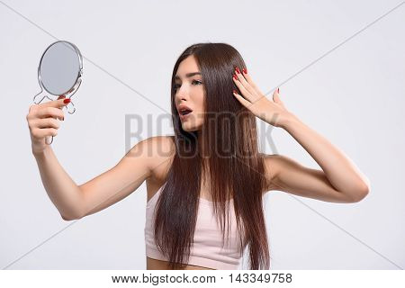 I am beautiful. Pretty young woman is looking at mirror with admiration. She is standing and touching her smooth hair. Isolated