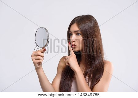 Hush. Young girl is raising finger to mouth secretly. She is standing and looking at mirror