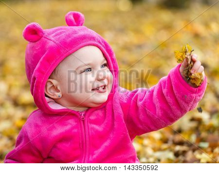 Adorable baby girl sitting in autumn leaves
