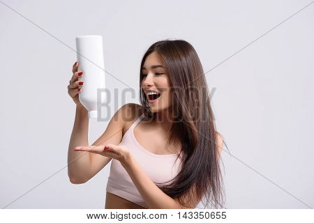 Happy girl is holding bottle and squeezing shampoo on hand. She is standing and smiling with admiration. Isolated