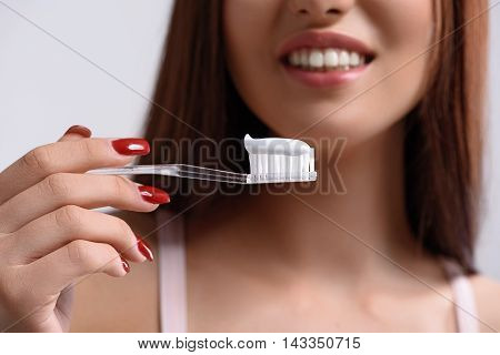 Close up of happy girl is holding toothbrush with toothpaste. She is standing and smiling. Focus on brush