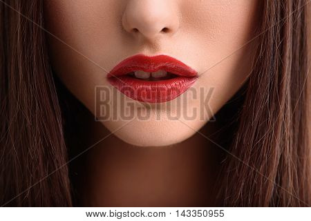 Close up of voluptuous female red lips. Woman has long brunette hair