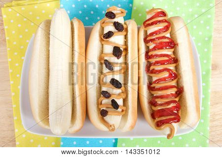 banana dog sandwiches on a rectangular plate with yellow green and blue polka dot napkins underneath. Banana in a hot dog bun plain with peanut butter and raisins peanut butter and jelly. Top view