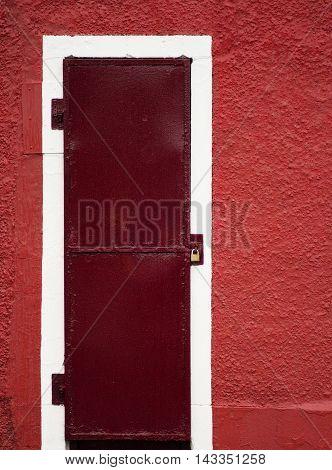 Padlocked reddish door in a red wall