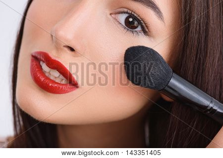 Close up of female face. Young woman is applying powder on her cheek. She is looking at camera and smiling