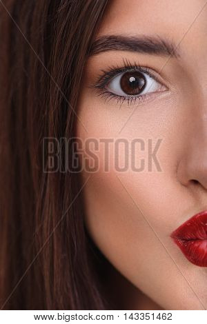 Close up of vertical half female face. Girl is making red lips in shape of kiss. She is looking forward with love