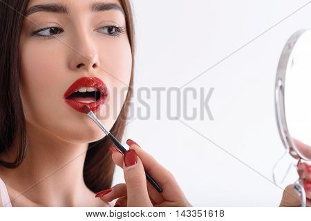 Sensual young girl is doing make-up in front of mirror. She is painting lips with concentration. Isolated