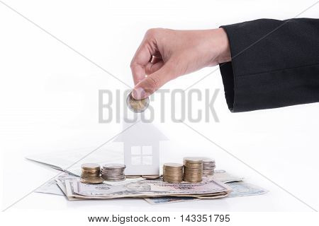 business hand holding money coin advertisement family home concept and growing pile coin money with account book for home finance and banking concept