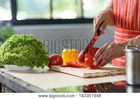 Close-up of young man cooking at home. He is standing and cutting pepper with knife