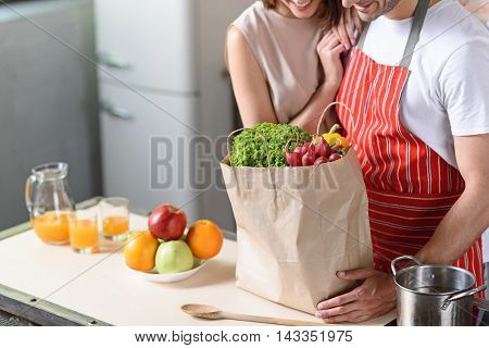 Joyful married couple prefers healthy eating. They are standing in kitchen and looking at fresh vegetables in shopping packet. Man and woman are smiling