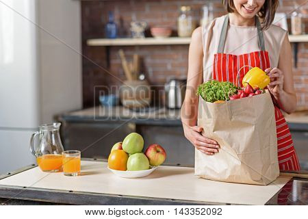 Young woman is preparing to cook healthy food. She is taking vegetables from packet and smiling. Lady is standing in kitchen and wearing apron