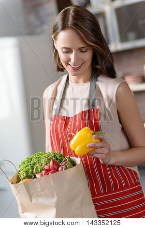 Cheerful woman is taking vegetables from shopping package. She is standing in kitchen and holding pepper. Housewife is smiling with happiness