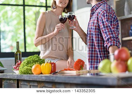 Cheers. Joyful married couple is clinking wineglasses and smiling. They are standing in kitchen and preparing dinner