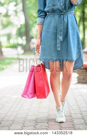Young woman is walking in park with shopping packets. Close up of her legs
