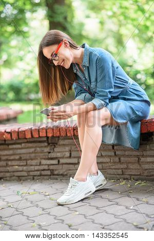 Happy young woman is listening to music from earphones. She is choosing song on smartphone and smiling. Lady is sitting on bench in park