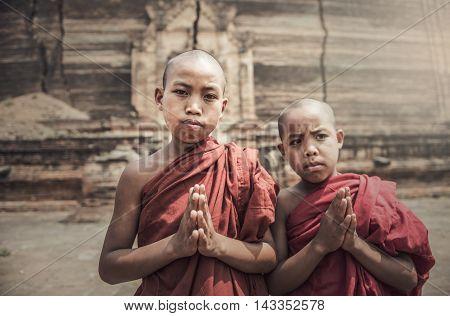 Young novice monk praying in temple, focus on hand, Bagan, Myanmar.