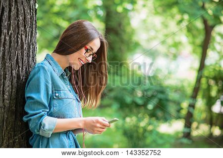 Happy girl is using mobile phone in park. She is standing and listening to music from earphones. Lady is smiling