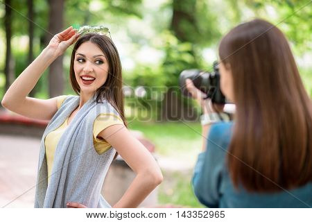 Professional female photographer is taking photos of woman. Young girl is standing in park and posing. She is smiling