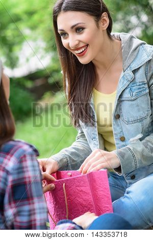 Cheerful young woman is giving present to her friend. Girl is opening packet and smiling happily. They are sitting in park