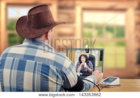 Cowboy with brown hat, checkered shirt sits at wooden desk takes blood pressure during internet session with virtual doctor in laptops monitor. Middle-aged man suffers hypertension. Rural doctor suggests one high blood pressure medication in white plastic