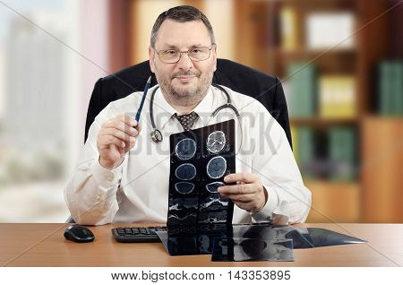 Mature male doctor wearing stethoscope around his neck explains brain x-rays and looks directly at the camera. Handsome bearded family physician with glasses, white shirt sits at office desk. There are keyboard, computer mouse and some x-rays on the desk