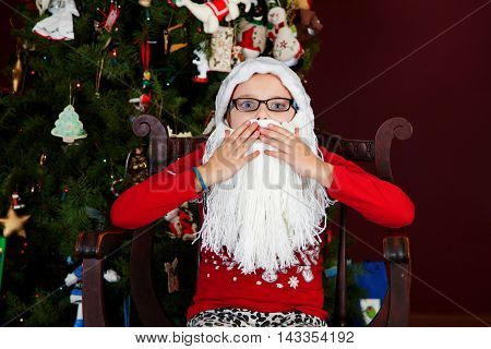 A young girl in a Santa Claus hat and beard looks startled and covers her mouth with wide blue eyes.