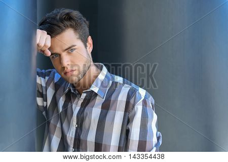 Young guy is standing and looking forward pensively